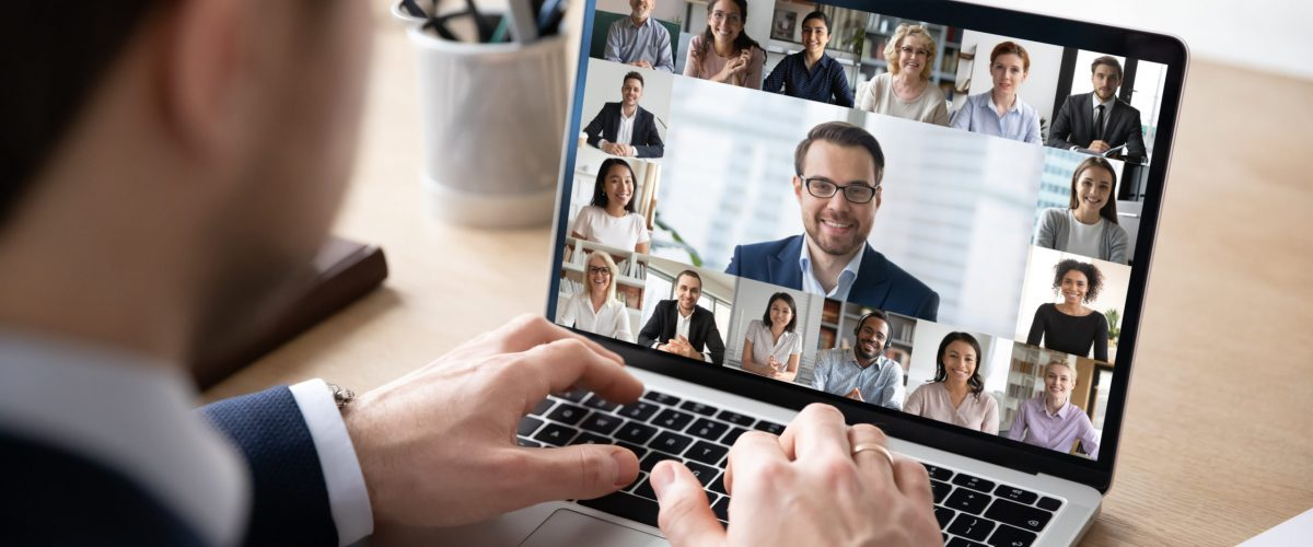 Rear view of businessman speak on web conference with diverse colleagues using laptop Webcam, male employee talk on video call with multiracial coworkers have online meeting briefing from home