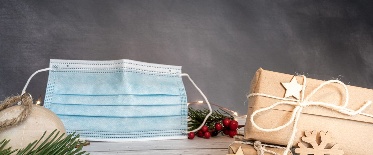 Christmas and zero waste, eco friendly packaging. wrapped gifts in craft paper and Christmas decoration on a wooden table. Blue surgical mask on grey background. ecological Christmas holiday concept, eco decor